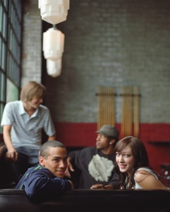 Four young adults sitting in booth (focus on couple in foreground)